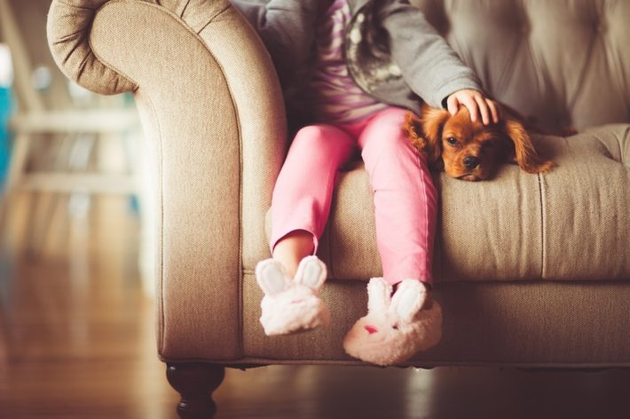child with slippers sitting next to a dog on a sofa