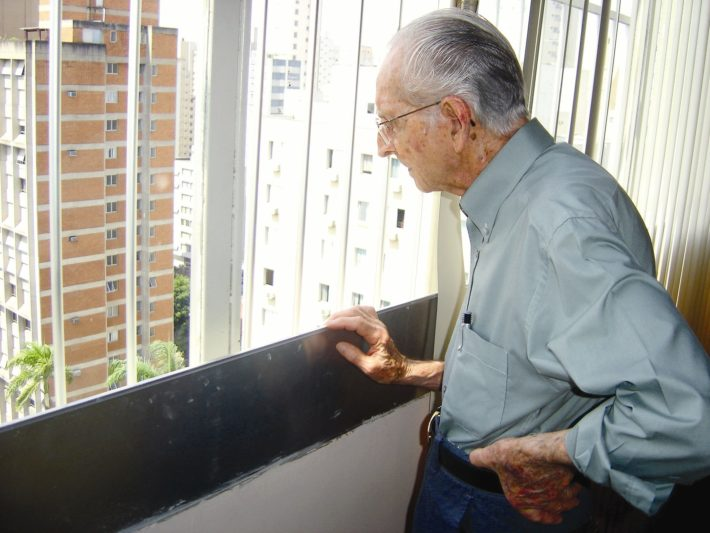 older man looking out of a window